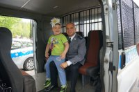 Komisarz Tomasz Obarski na wspólnej fotografii z niepełnosprawnym dzieckiem