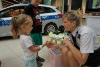Policjantka w trakcie wręczania dziecku odblasku