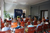 Sierżant Monika Śliwińska prezentuje dzieciom wyposażenie policjanta
